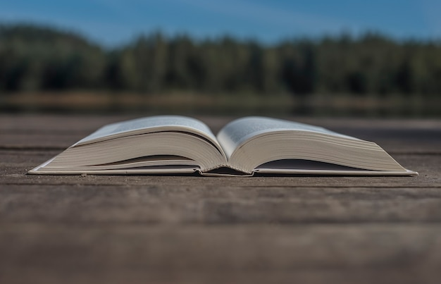 Offenes modernes buch auf holzschreibtisch mit kopienraum für text und naturlandschaft auf hintergrundkonzept von...