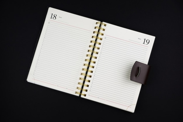 Offenes notizbuch aus braunem leder auf schwarzer oberfläche