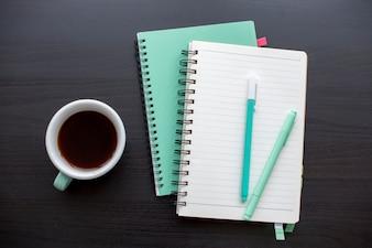 Offenes Notizbuch des tadellosen Grüns und eine Tasse Kaffee
