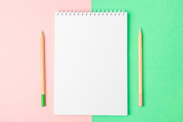 Offenes notizbuch des weiß auf den grünen und rosa hintergründen. in der nähe sind bleistifte.