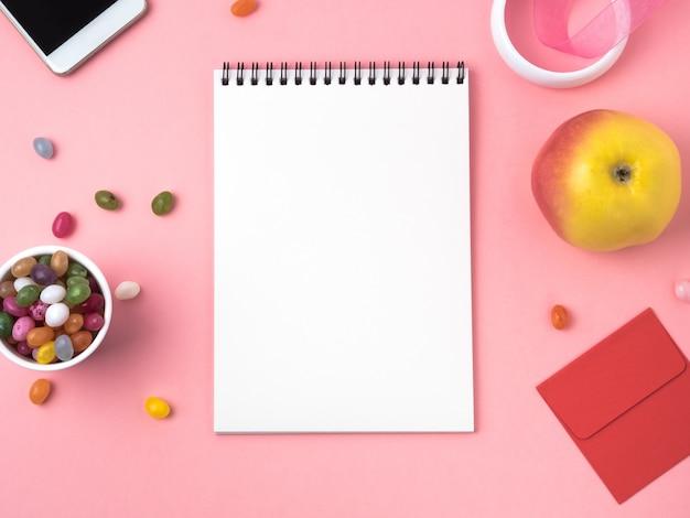 Offenes notizbuch mit einem sauberen weißen blatt, karamell, lutscher, telefon, apfel