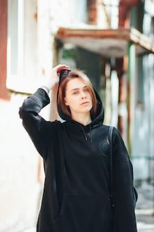 Offenes porträt des jungen schönen langen haarmädchenmode-modell-hippies im schwarzen kapuzenpulli auf stadt