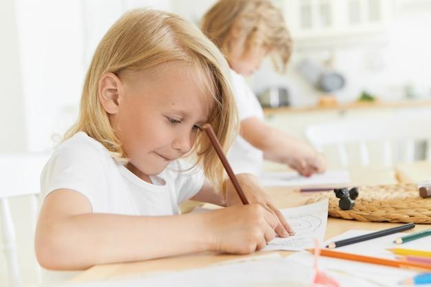 Offenes porträt von zwei vorschulkindern, die freizeit drinnen zu hause oder im kindergarten verbringen, die zusammen am hölzernen schreibtisch mit bleistiften und blatt papier sitzen, zeichnung. entwicklung und kreativität