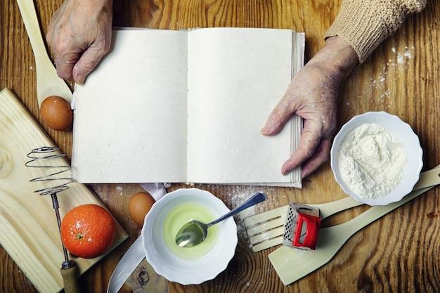 Offenes rezeptbuch in den händen einer älteren frau vor einem tisch mit utensilien