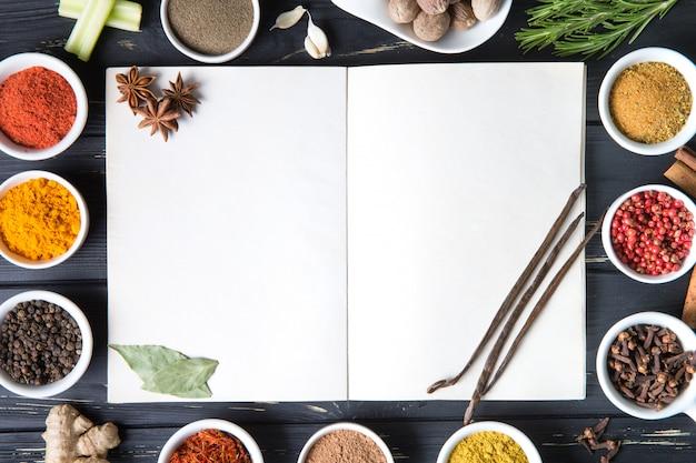 Offenes rezeptbuch mit frischen kräutern und gewürzen