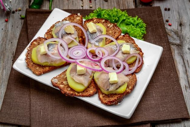 Offenes sandwich mit hering, zwiebel, kartoffel und butter