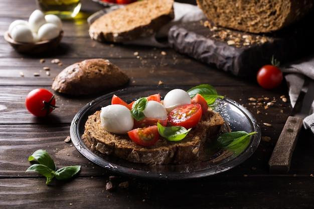 Offenes sandwich mit tomaten, mozzarella und basilikum