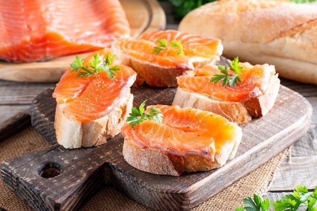 Offenes sandwich, toast mit lachs, butter auf dem tisch. gesundes frühstück des morgens mit fisch, seitenansicht,