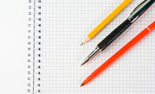 Offenes schreibbuch mit kugelschreiber, bleistift und rotem marker
