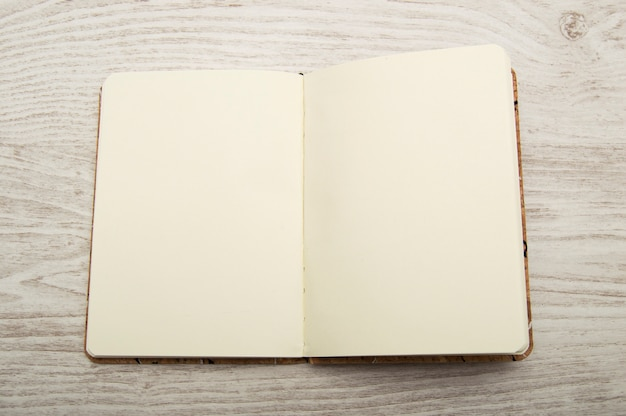 Offenes und leeres notizbuch auf holztisch