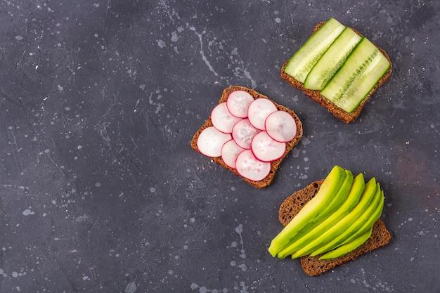 Offenes vegetarisches superfood-sandwich mit verschiedenen belägen: avocado, gurke, rettich auf dunklem hintergrund. gesundes essen. bio- und vegetarisches essen. flache lage, kopierraum für text, minimalismus