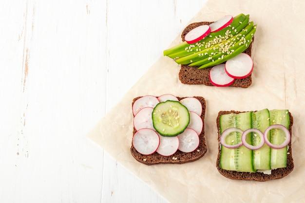 Offenes vegetarisches superfood-sandwich mit verschiedenen belägen: avocado, gurke, rettich auf einem papier auf weißem hintergrund. gesundes essen. bio- und vegetarisches essen