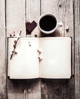 Offenes vintage-buch mit blütenzweig aus kirschbaum, pralinen und kaffeetasse