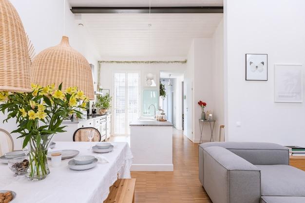 Offenes wohn- und esszimmer mit flachbildfernseher, grauem sofa und holztisch mit trendigen stühlen
