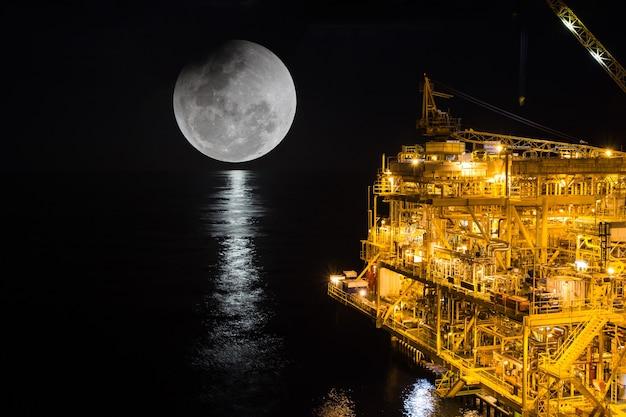 Offshore die nachtindustrie öl- und gasproduktion erdölpipeline hintergrund super blauer blutmond