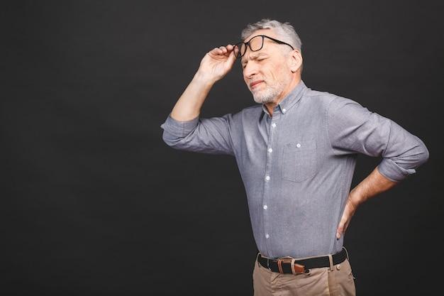 Oh, ich brauche eine massage! porträt eines älteren mannes, der rückenschmerzen vor einem schwarzen hintergrund hat.