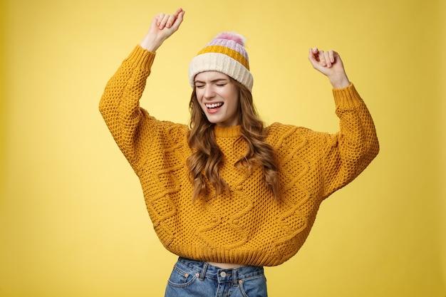 Oh ja partystimmung. portrait fröhliches unbeschwertes tanzendes glückliches mädchen mit wintermützenpullover, das spaß hat, die hände zu heben und sich bewegenden musikrhythmus zu tanzen, der den erfolg feiert positive nachrichten