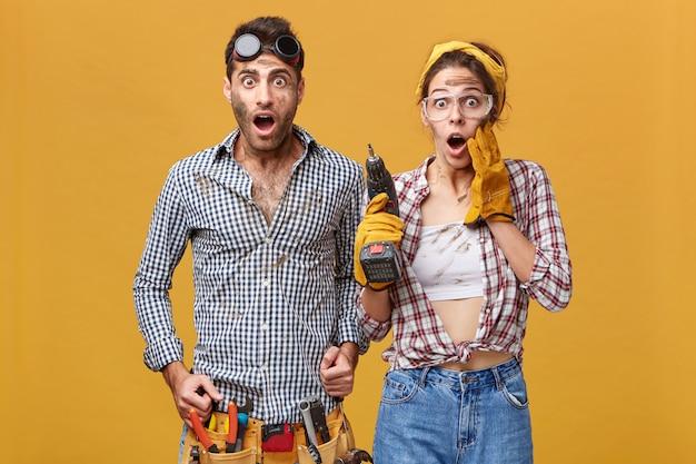 Oh mein gott! beeindruckend! porträt emotional überraschter junger europäischer servicetechniker, die eine schutzbrille tragen, die ungläubig aussieht, den mund weit offen hält und die augen herausspringt