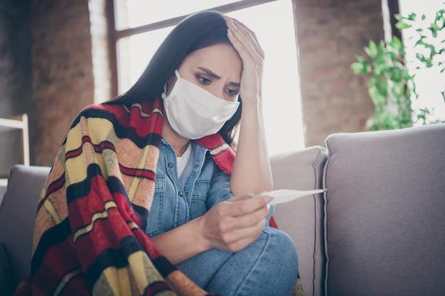 Oh nein, ich habe corona-virus. frustrierte panik schockiert mädchen fühlen schmerz messen temperatur covid19 sarscov2 symptom berühren hand kopf sitzen couch plaid decke abdeckung jeans hemd im haus drinnen