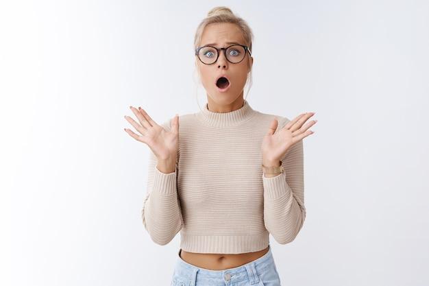 Oh nein, katastrophe. porträt einer schockierten, ängstlichen und überwältigten besorgten europäischen frau mit blonden haaren in brille, die mit offenem mund keucht und gestikuliert, zittert und entsetzt über die weiße wand?