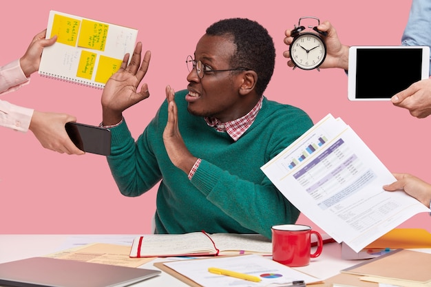 Oh nein, nicht jetzt! gestresster dunkelhäutiger mann hat viel arbeit im büro, gefragt von vielen leuten auf einmal, die an die vorbereitung eines geschäftsprojekts erinnern, wecker halten