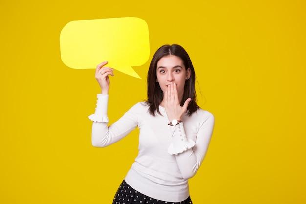 Oh nein oder ups geste gemacht von einem jungen schönen mädchen, das eine sprechblase auf gelbem raum hält.