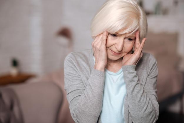 Oh, nicht schon wieder. nahaufnahmeporträt der sehr traurigen älteren frau, die ihre schläfen wegen schrecklicher kopfschmerzen berührt.