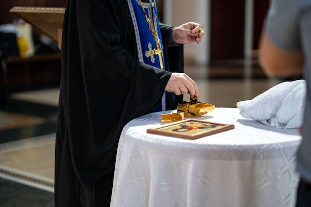 Ohne gesicht. priester mit öl zur salbung bei der taufe. religiöse traditionen und rituale.