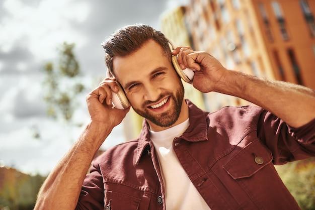 Ohne musik kann man nicht leben. schöner und glücklicher junger mann mit stoppeln in kopfhörern, der musik hört und lächelt, während er auf der straße steht. inspiration. musikkonzept. klang