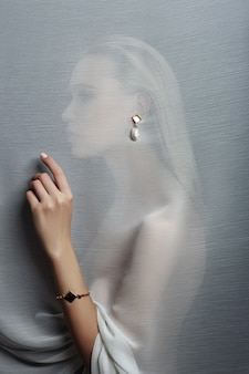 Ohrringe und schmuck im ohr einer sexy frau durch einen transparenten stoff gesteckt. perfektes blondes mädchen, wunderschöner mysteriöser look. werbeschmuck, schöne ohrringe im mädchenohr