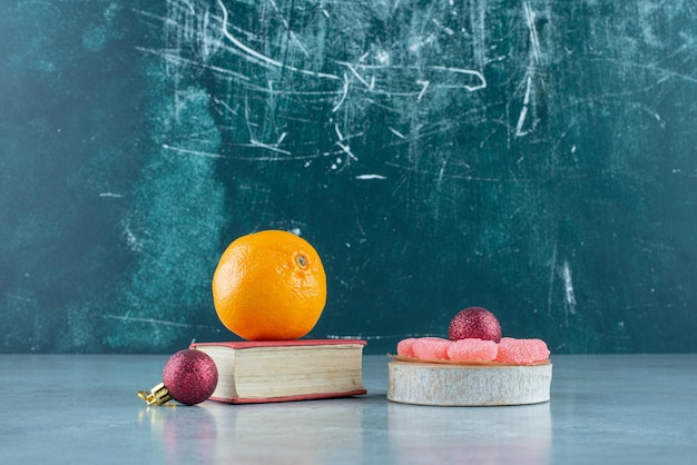 Oirange auf einem buch, marmeladen auf einem holzstück und zwei zierkugeln auf marmor.