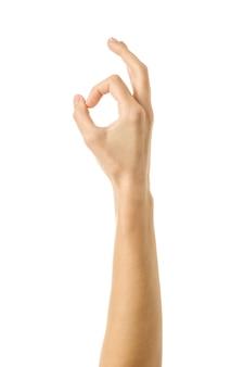 Ok zeichen. frauenhand mit französischer maniküre gestikuliert lokalisiert auf weißer wand. teil der serie
