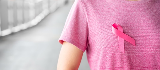 Oktober-brustkrebs-bewusstseinsmonat, frau im rosa t-shirt mit rosa band für das stützen der lebenden leute und der krankheit. gesundheitswesen, internationaler frauentag und weltkrebstagskonzept