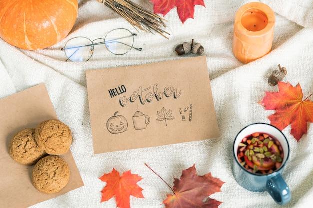 Oktober mit herbstlaub, essen und trinken, eicheln, kerze und brille auf handtuch