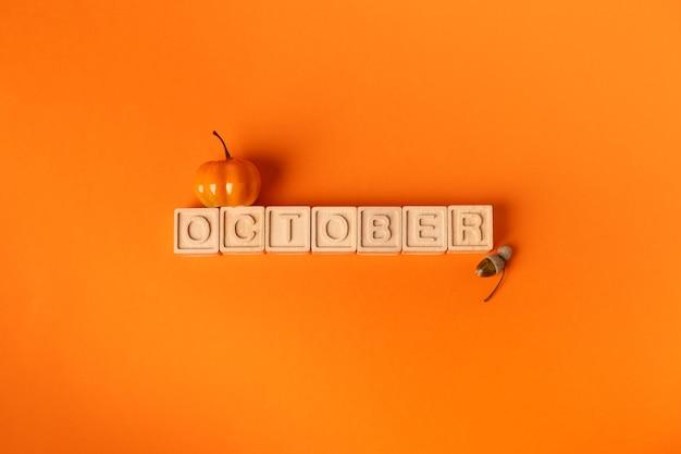 Oktober-wort auf holzklötzen und kleinem kürbis und eichel orange hintergrund