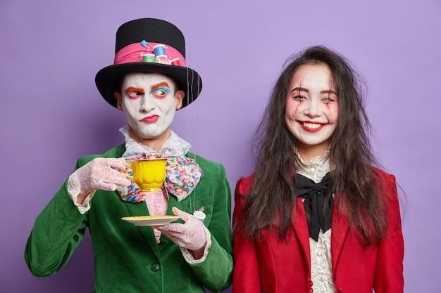 Oktoberferien. ernsthafter unzufriedener hutmacher trinkt tee-posen nahe fröhlicher brünetter frau mit schädel-make-up