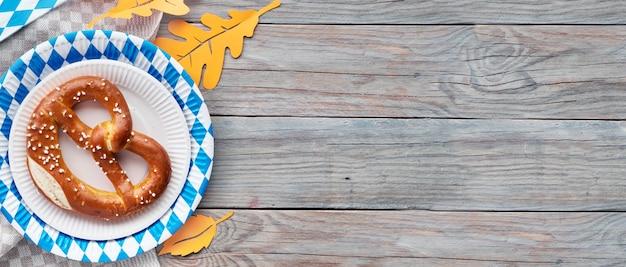 Oktoberfest, flach auf rustikalem holztisch mit brezel und herbstdekoration