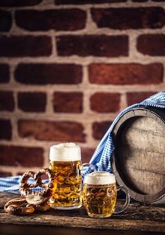 Oktoberfest großes und kleines bier mit brezelholzfass und blauer tischdecke.
