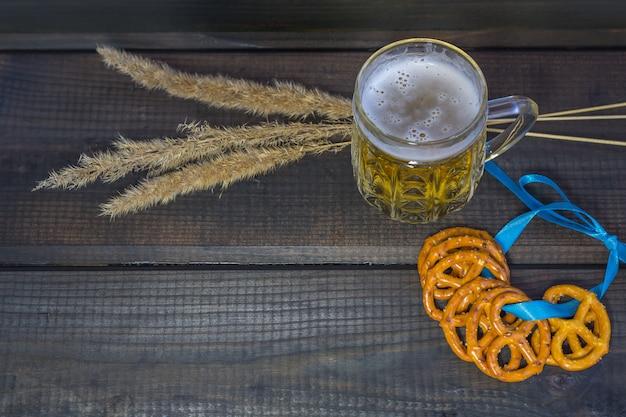 Oktoberfest-konzept. bierkrug mit snäcken von salzbrezeln, von brezel und von blauem band auf einem dunklen holztisch.