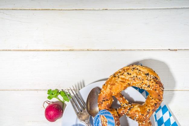 Oktoberfest-konzept. oktoberfest-gedeckhintergrund, tellergabelmesserlöffel mit traditioneller serviette, bierkrug. serviert bei veranstaltung, bar-menü flatlay, weißer holztisch kopie raum draufsicht