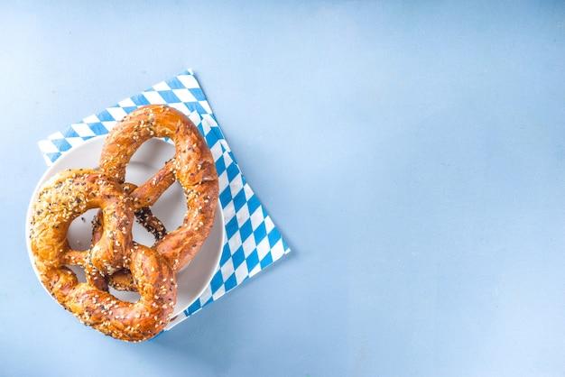 Oktoberfest-konzept. oktoberfest-tischhintergrund, tellergabellöffel mit traditioneller serviette, serviert bei veranstaltung, barmenü-flatlay, bunter blauer tischkopierraum draufsicht