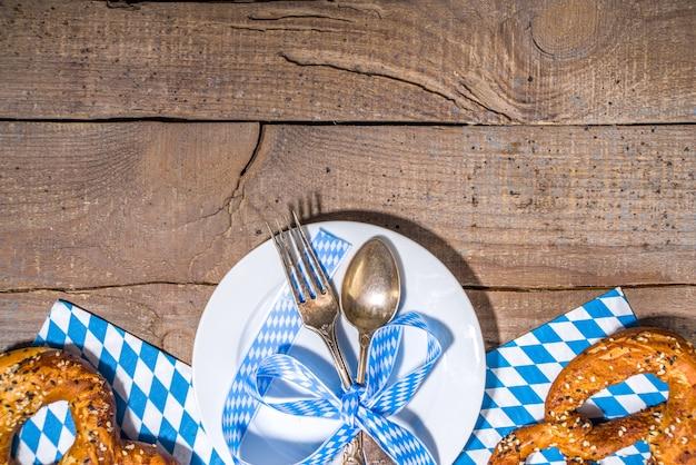 Oktoberfest-konzept. oktoberfest-tischhintergrund, tellergabellöffel mit traditioneller serviette, serviert bei veranstaltung, barmenü-flatlay, weißer holztisch kopienraum draufsicht