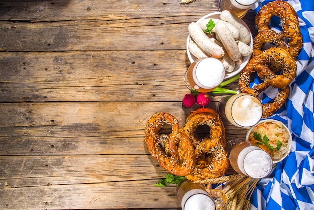 Oktoberfest-lebensmittelhintergrund, traditionelles bayerisches feiertagsmenü, würstchen mit brezeln, sauerkraut, bierglas und tassen auf hölzernem sonnenbeleuchtetem hintergrundkopierraum draufsichtkopierraum