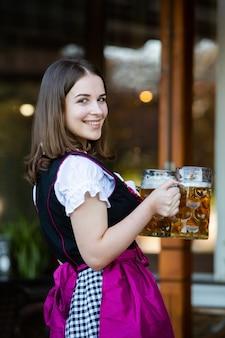 Oktoberfestfrauen, die ein traditionelles bayerisches kleid tragen, das bierkrüge hält