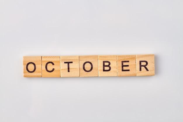 Oktoberwort geschrieben auf holzklötzen. auf weißem hintergrund isoliert.