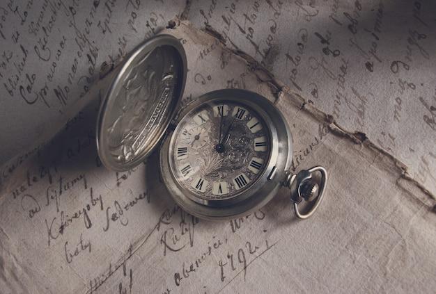 Old-time-uhr, aktuelle uhrzeit, handschriftliche dokumente, geschichte