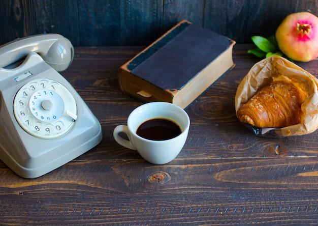 Old vintage telefon, kaffee, buch, auf einer holzoberfläche,