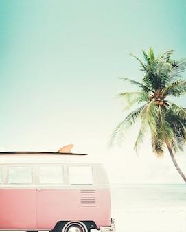 Oldtimer parkte auf dem tropischen strand (meer) mit einem surfbrett auf dem dach