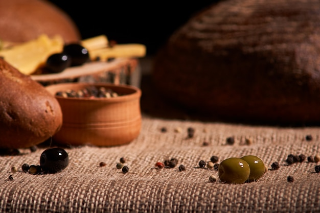 Olive steht auf dem tisch im hintergrund mit brot, baguette und käse. tiefenschärfe