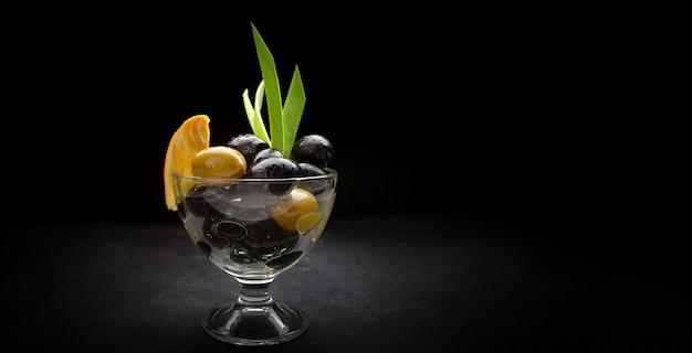 Oliven auf schwarzem grund, in einer glasschüssel, mit einer scheibe orangen- und frühlingszwiebelblättern